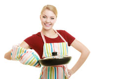 Housewife or chef in kitchen apron with skillet frying pan Stock Images