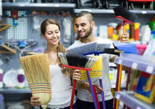Housewife chooses broom for cleaning Stock Image