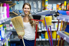 Housewife chooses broom for cleaning Royalty Free Stock Photos