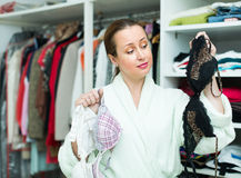 Housewife choosing underwear. Happy housewife checking out underwear at family cloakroom Royalty Free Stock Image