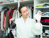 Housewife choosing underwear. Happy woman checking out underwear at family cloakroom Stock Photo