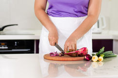 Housewife chopping vegetables in the kitchen Stock Photos