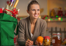 Housewife with christmas shopping bag in kitchen Stock Images