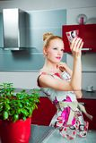 Housewife with clean glass in interior of kitchen Royalty Free Stock Photography
