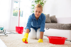 Housewife cleaning carpet with brush and doing housework Royalty Free Stock Images
