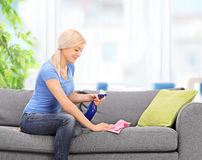 Housewife cleaning a couch with a rag Royalty Free Stock Photos