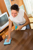 Housewife cleaning furniture at cabinet Stock Photos