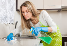 Housewife cleaning furniture in kitchen Royalty Free Stock Images