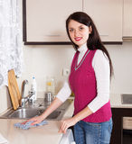 Housewife cleaning  furniture in kitchen Royalty Free Stock Image