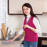 Housewife cleaning  furniture with rag in kitchen Royalty Free Stock Photos