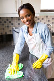 Housewife cleaning kitchen. Attractive african housewife cleaning the kitchen stock photo