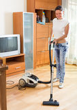 Housewife cleaning room with vacuum cleaner Royalty Free Stock Photo