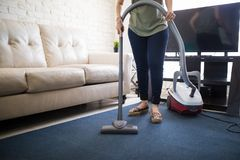 Housewife cleaning rug in living room. Closeup of hand and legs of a woman using vacuum cleaner to clean living room carpet dust Stock Photo