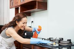 Housewife cleaning stove. Housewife spraying stove with detergent before wiping it royalty free stock photo
