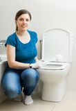 Housewife cleaning toilet bowl with brush in bathroom Royalty Free Stock Photography