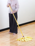 Housewife cleaning wooden floor by mop Stock Photography