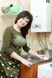 Housewife cleans the kitchen sink. With melamine sponge royalty free stock photo