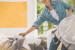 Housewife collects scattered clothes. Smiling housewife collects scattered clothes and prepares them for laundering royalty free stock photography