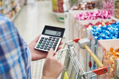 Housewife considers costs in store Royalty Free Stock Photography