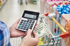 Housewife considers costs in store Stock Images