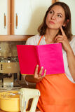 Housewife with cookbook in kitchen. Royalty Free Stock Image