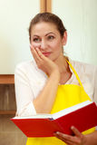 Housewife with cookbook in kitchen. Royalty Free Stock Photos