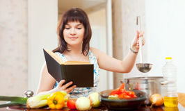Housewife cooking with book Royalty Free Stock Image