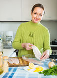 Housewife cooking filleted fish Royalty Free Stock Photo