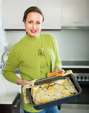Housewife cooking filleted fish. Happy housewife cooking filleted fish at kitchen Royalty Free Stock Photos