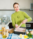 Housewife cooking filleted fish. Happy smiling woman cooking filleted fish at home kitchen Stock Image