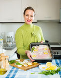 Housewife cooking filleted fish. Positive housewife cooking filleted fish at kitchen Royalty Free Stock Images