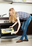 Housewife cooking fish on sheet pan in oven at home Stock Image