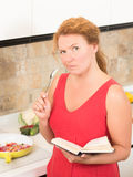 Housewife cooking in the kitchen. Serious housewife tasting the meal she is cooking in the kitchen. Lady holding recipe book and having desire to add more salt Stock Images