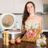 Housewife cooking meat with multicooker Royalty Free Stock Photos