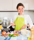 Housewife cooking meat with rice at kitchen. Housewife cooking meat with rice at domestic kitchen Royalty Free Stock Photos