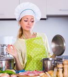 Housewife cooking with meat Stock Photography