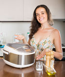 Housewife cooking with multi cooker Royalty Free Stock Images