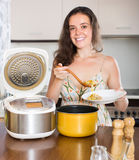 Housewife cooking with multi cooker Royalty Free Stock Image