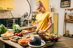 Housewife cooking, organic food preparation. Housewife cooking on the kitchen, healthy organic food preparation. Vegetarian diet, fresh vegetables and fruits on royalty free stock image