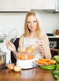 Housewife cooking potatoes with electric steamer Stock Photography