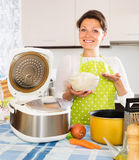 Housewife cooking rice with multicooker Stock Photos