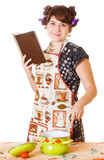 Housewife cooking a soup. Young housewife cooking and reading a cookbook Stock Image