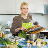 Housewife cooking soup with  fish Stock Photos
