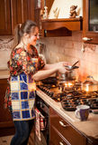 Housewife cooking soup in saucepan Royalty Free Stock Image
