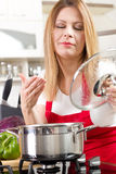 Housewife cooking and testing the food in  kitchen Royalty Free Stock Photo