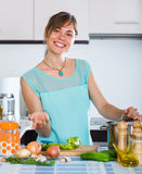 Housewife cooking vegetables. Happy girl cooking vegetables basing on new recipe indoors Royalty Free Stock Photo