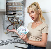 Housewife counts up money for repair of a gas water heater Stock Image