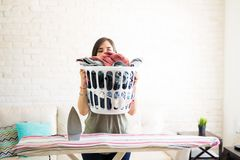 Young woman holding laundry basket. Housewife covering face with heavy laundry basket and keeping on iron table Royalty Free Stock Photo