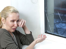 Housewife cries, bad quality window has burst because of cold weather Stock Photo
