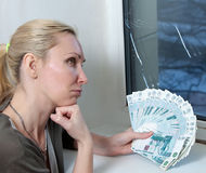 The housewife cries and counts money for repair of a window which has burst in a frost Royalty Free Stock Image